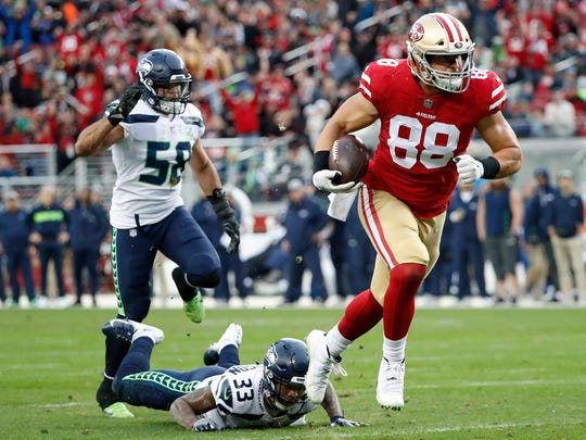San Francisco 49ers tight end Garrett Celek (88) runs past Seattle Seahawks free safety Tedric Thompson (33) and outside linebacker Austin Calitro (58) to score against the Seattle Seahawks during the first half of an NFL football game in Santa Clara, Calif., Sunday, Dec. 16, 2018. (AP Photo/Tony Avelar)