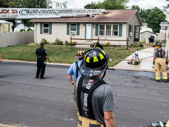 Firefighters look on after putting out a fire Sunday afternoon on Elm Lane, in Oxford township, Sunday, July 16, 2017. The fire started in the kitchen area and took crews about 15 minutes to extinguish.