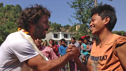 In this Tuesday, May 5, 2015 photo, Portuguese Lourenco Macedo Santos, left, is welcomed by villagers at Ichangu Narayan on the outskirts of Kathmandu, Nepal. Using funds pledged through a Facebook appeal, two Portuguese men Pedro Queiros and Santos are taking food and bedding to needy Nepalis made homeless by the magnitude 7.8 earthquake that struck just outside Kathmandu shortly before noon on April 25. (AP Photo/Johnson Lai)