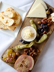 House charcuterie and fromage appetizer with duck and port galantine with two kinds of cheese and house pickles by La Petite Pierre, French bistro and wine bar at 7800 Camargo Road, Madeira. Monday April 9, 2018.