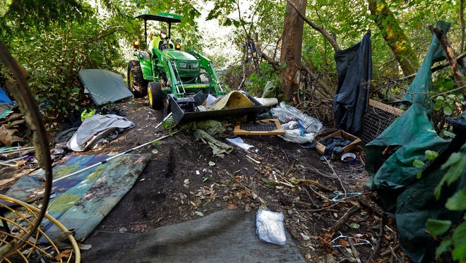 In this Sept. 26, 2017 photo, a worker uses a tractor to clear a large homeless encampment in the woods near Seattle's Ravenna Park neighborhood. Residents were given notice and offered shelter beds and other services, but some people in the encampment did not remove their belongings before the cleanup began. Seattle is just one of the cities on the West Coast facing a homeless crisis of unprecedented proportions.