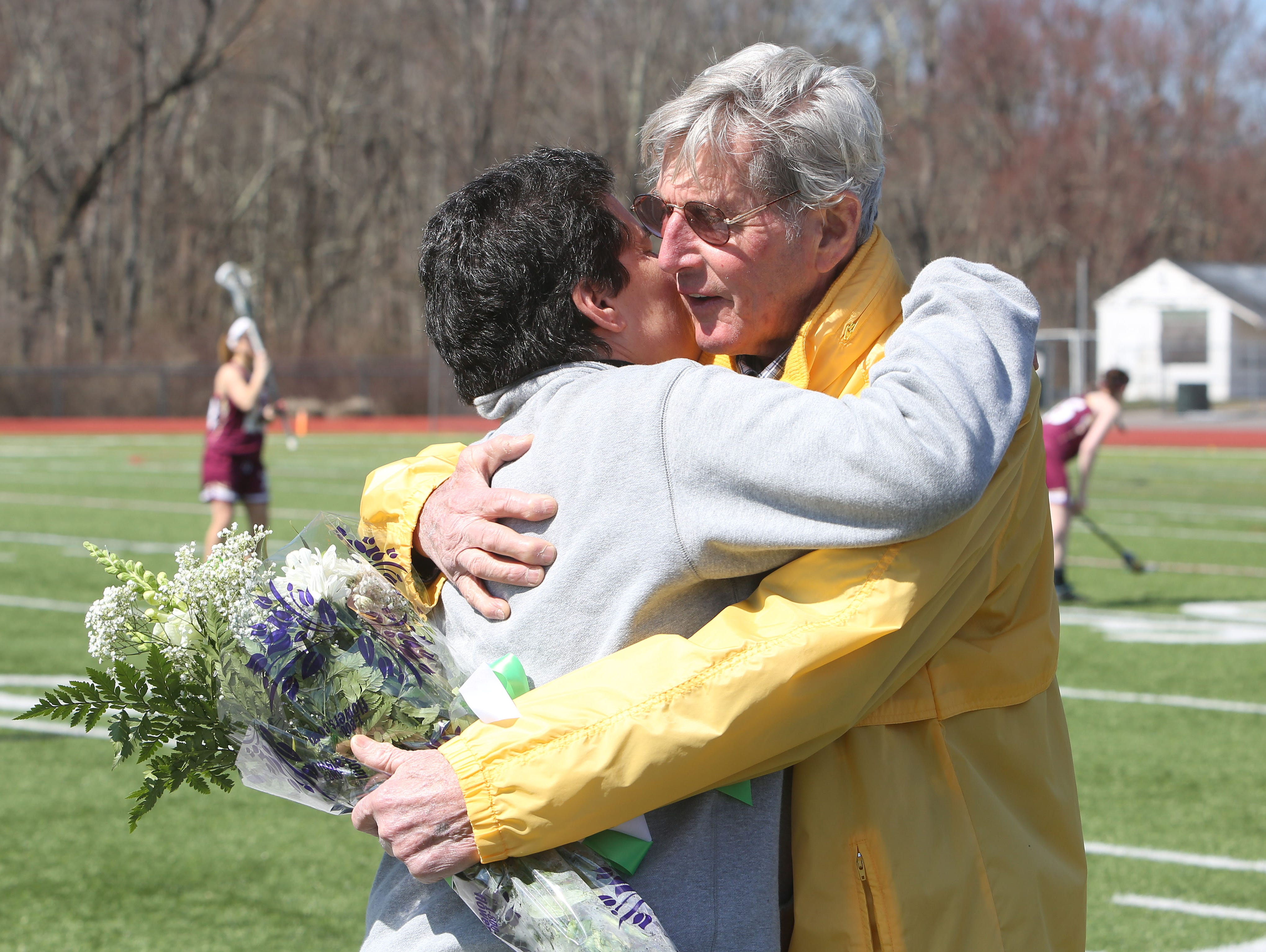 From right, Former Yorktown girl's lacrosse coach Bill Robertson gets a hug from present girl's coach Ellen Mager during a halftime ceremony honoring the past state championship teams at Yorktown High School during game against Arlington March 26, 2016.
