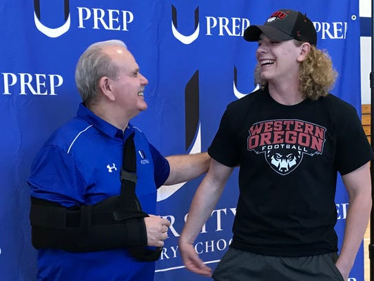 U-Prep football player Dawson Gruhler, right, receives