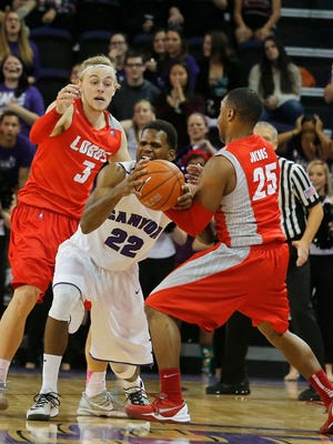 Grand Canyon guard Royce Woolridge (22) battles for the ball with New Mexico guard Hugh Greenwood (3) and Tim Jacobs (25) during the second half on Tuesday, Dec. 23, 2014, in Phoenix.