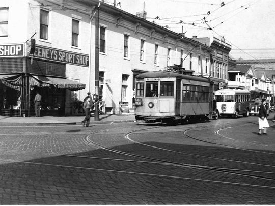 A streetcar and bus are pictured at Columbus and Main streets in 1937, when the trolley system was being replaced by the bus system.