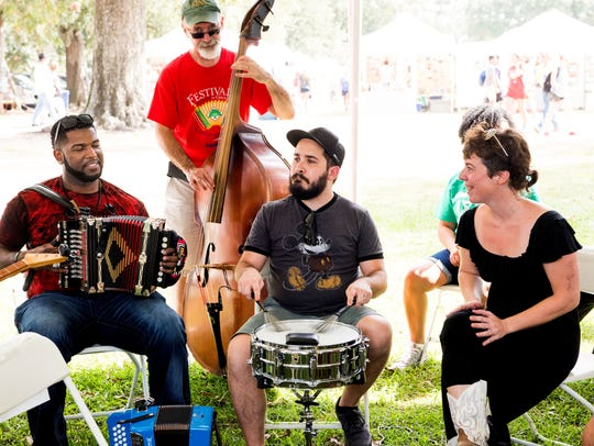 Zydeco musician Lil Nate, left, discusses and demonstrates