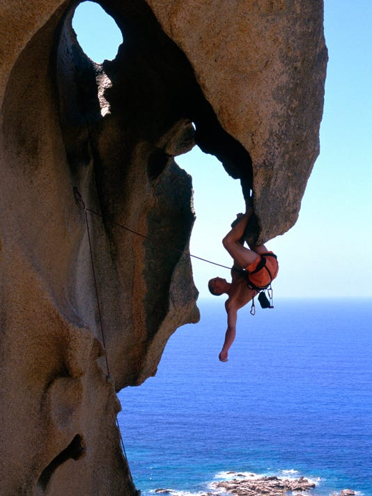 Side profile of a man hanging upside down on a cliff