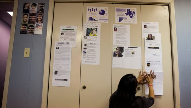 Erika Reyna Brodhag, prevention and education manager for The Purple Door, adds a Caller-Times article about the murder of Yvonne Villanueva to a wall of articles written by the newspaper about domestic violence murders in Corpus Christi on Monday, June 18, 2018. She uses the articles while teaching a BIP course, which offenders take, at the organization.