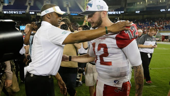 South Florida head coach Willie Taggart, left, talks with Western Kentucky quarterback Brandon Doughty (12) after the NCAA college football Miami Beach Bowl game, Monday, Dec. 21, 2015, in Miami. Kentucky defeated South Florida 45-35. Taggart was a former head coach for Western Kentucky. (AP Photo/Lynne Sladky)