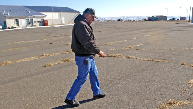 In a file photo from Jan. 21, 2013, Mike Arnold, manager of the Aztec Municipal Airport, points out damage to the airport that needs repairs. The pilots lounge, pictured in the background, will be named after Arnold, who died in May 2013.