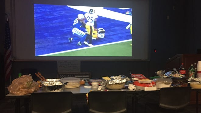 Dinner spread and football on the projection screen during RPD's Lake Section Thanksgiving meal on Thursday.