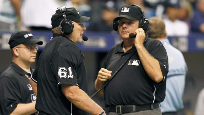 Umpire Bob Davidson and Jerry Lane wait for a response on an instant replay call.