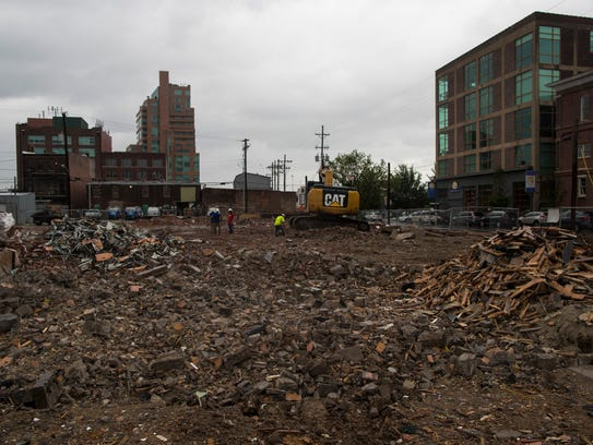 Construction crews work on cleaning up debris after