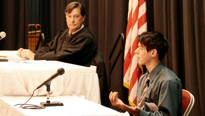 Tulare County Superior Court Judge Gary Paden, left, looks on as a Tulare Union High School student plays the role of a graduate student, accused of stealing an expensive painting, for the county Mock Trials.