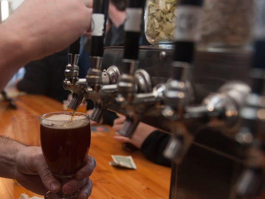 A beer is poured at the Lunacy Brewery in Magnolia.