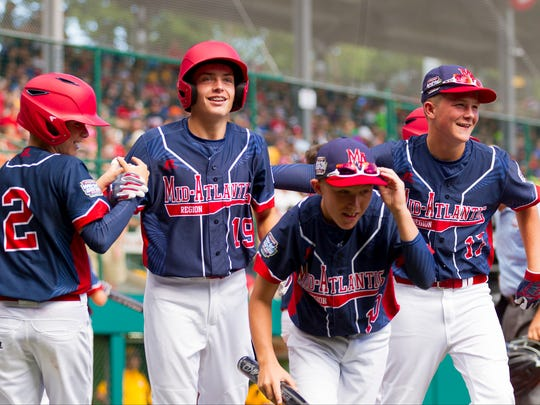 From left, Maine-Endwell's Billy Dundon, left, congratulates Ryan Harlost after his first inning home run as Justin Ryan and Jayden Fanara, also join the celebration. Maine-Endwell won 3-1 to advance at the Little League World Series.