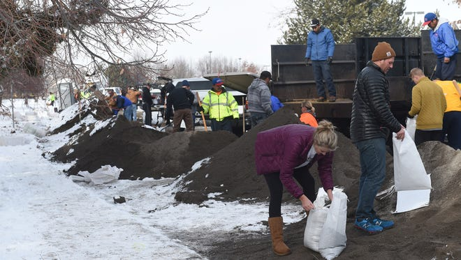 People fill sandbags Saturday while preparing for a potential flood around the Sparks Industrial Complex.