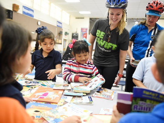 Volunteers Katy Holmes, center right, and Amy Malkovich, right, help students Yamileth Trejo Gutierrez (blue) and Mary Sing (stripes) pick books during a book delivery by Ride for Reading to students at Haywood Elementary School April 22, 2016 in Nashville, Tenn. Ride for Reading puts books in the hands of low-income children via bicycle, promoting literacy and healthy living.