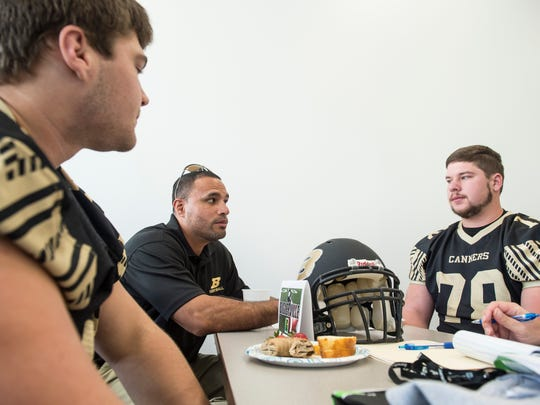 (Clockwise) Biglerville's Brent Hayes, head coach Alex Ramos and Paul Asper speak with a member of the media during the YAIAA football media day in Hanover on Tuesday, August 1, 2017.