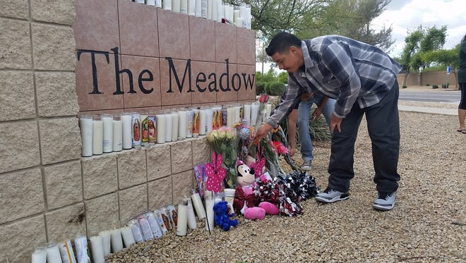 A Sierra Linda High School student places flowers Sunday, April 26, 2015, at a memorial set up for three Sierra Linda High students injured in a car accident last week.
