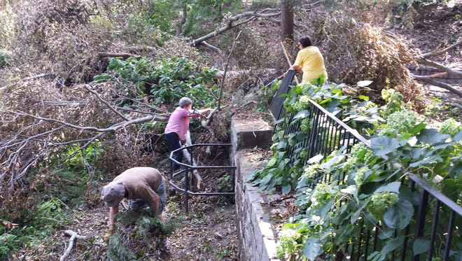 Volunteers work to clear damage from a summer storm at the Kilgore-Lewis House.  Proceeds from an upcoming plant sale will help to restore the gardens.