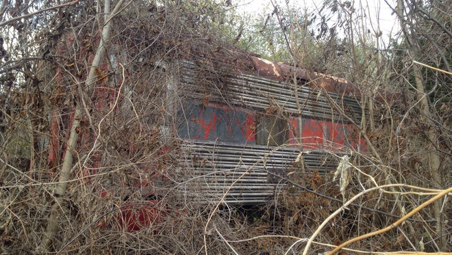 An old Frisco Railroad car sits in a junkyard off of West Division Street.