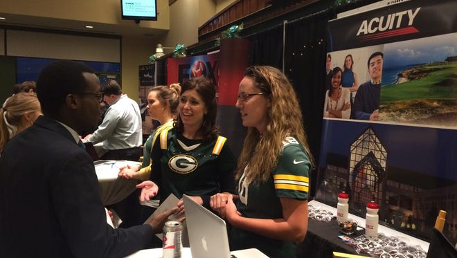 Marc Minani, left, talks with Acuity human resources employees Tracy Wusterbarth, center, and Amanda Gebert during Thursday's Internship Draft Day at Lambeau Field.