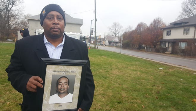 Gregory Lee Wilson holds a photo of his 34-year-old son, Gregory Lee Wilson Jr., at the corner of 30th Street and Capitol Avenue, just footsteps from where his son was fatally shot on Oct. 28.