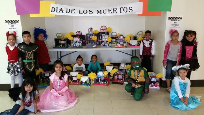 Hillcrest Elementary first graders posed with their altares they made in class.