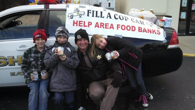 Sgt. Jim West of the Eaton County Sheriff's Department and some of the kids he caught up with during last year's Fill a Cop Car food drive at Carl's Super Market in Dimondale.