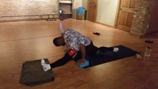 Packers defensive lineman B.J. Raji does the splits during a yoga session Friday at Flow Yoga Studio in De Pere.