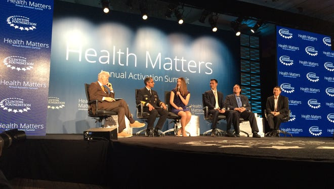 Former President Bill Clinton, left, listens to panelists during the opening session of the fifth annual Clinton Health Matters Initiative Activation Summit in Indian Wells.