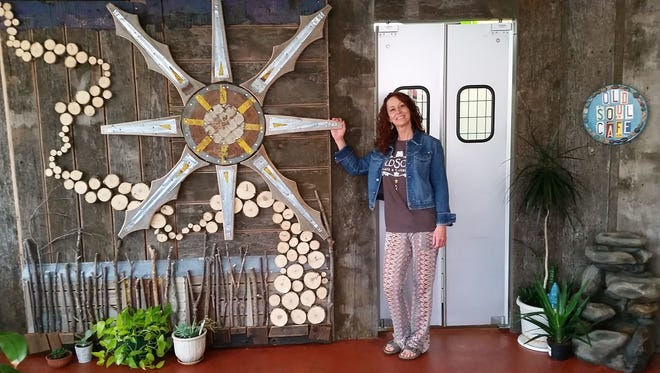 Old Soul Cafe owner Shonna Haugen stands by an upcycled decoration she made for her restaurant out of barn wood and other materials. Old Soul will open in July.