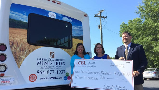 Citizens Building & Loan's Jennifer Jones, left, and Dennis Trout, right, present Greer Community Ministries' Cindy Simpler with a check covering the cost of the nonprofit organization's new bus.