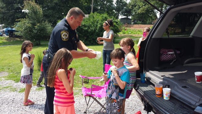 Lt. Tobin Tech of QRT and York Area Regional Police hands out honorary badges to kids following a six-hour standoff in their neighborhood.