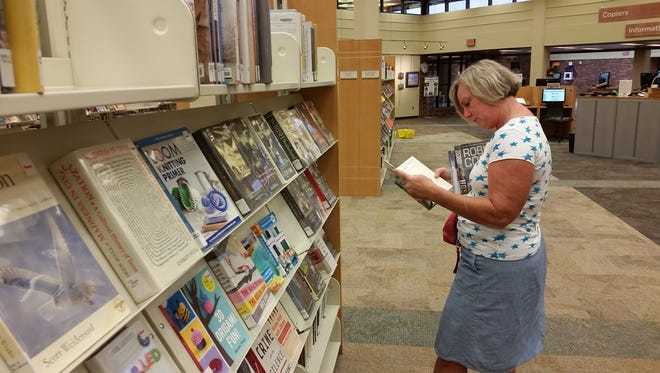Carolyn Kolhoff browses books at the Downtown Library in search of an autobiography to read within the next few weeks.