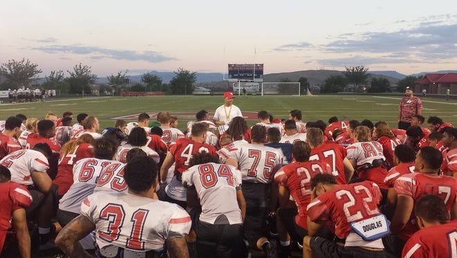Dixie State head coach Shay McClure addresses his team at the end of practice before Thursday's game against New Mexico Highlands.