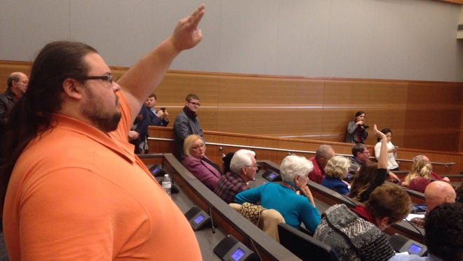 Mike Carlson raises his hand to ask a question to lawmakers about his concerns that he'll lose his Affordable Care Act coverage during a Middle Tennessee State University College Republicans event.