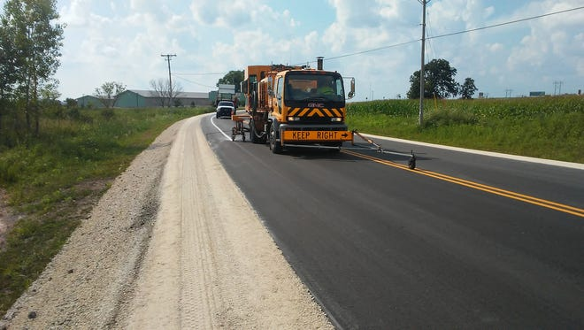 John Hofman, pavement marking foreman, is pictured driving the truck, while John Scheberl operates the paint applicator of the County's centerline pavement marking machine, on County Highway I.