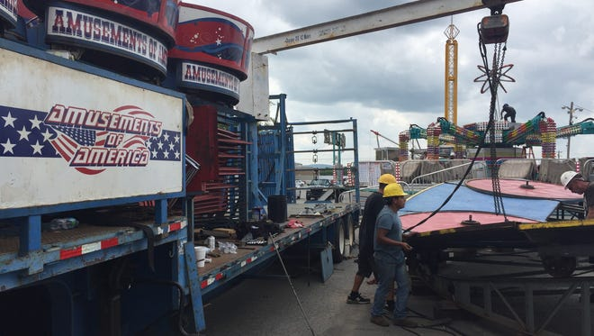 Workers set up rides provided by Amusements of America at the Wilson County Fair on Aug. 15, 2017.