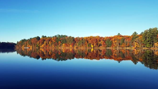 Fall colors line the shore of Lower Kaubashine Lake in Hazelhurst.
