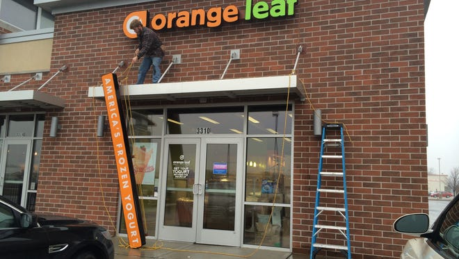 A worker removes signs from the Grand Chute Orange Leaf shop on Sunday, Nov. 23, 2014.