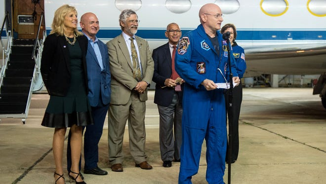 In this photo provided by NASA, Jill Biden, wife of Vice President Joe Biden, left, Mark Kelly, former NASA astronaut and Scott Kelly's identical twin, second from left, Dr. John Holdren, director of the White House Office of Science and Technology, third from left, NASA Administrator Charles Bolden, fourth from right, and Ellen Ochoa, director, NASA's Johnson Space Center, watch as Expedition 46 Commander Scott Kelly of NASA speaks at Ellington Field, Thursday, March 3, 2016, in Houston, after his return to Earth. Kelly returned to Earth on Wednesday after an unprecedented year in space for NASA, landing in barren Kazakhstan with a Russian cosmonaut who shared his whole space station journey.