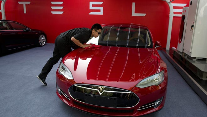 A worker on Tuesday cleans a Tesla Model S sedan before the event with CEO Elon Musk to deliver the first eight of Model S electric cars to customers in Beijing, China.