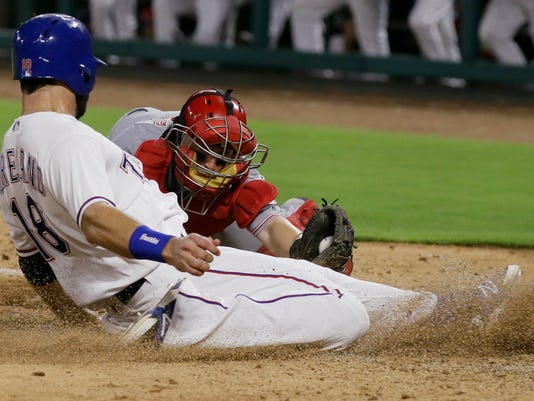 Texas Rangers' Mitch Moreland (18) is tagged out at home plate by Cincinnati Reds catcher Tucker Barnhart during the first inning of a baseball game in Arlington, Texas, Tuesday, June 21, 2016. The Reds won 8-2. (AP Photo/LM Otero)