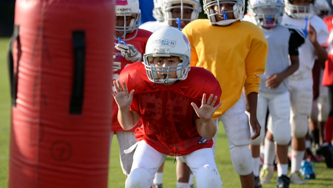 Mason Mitchell, 9, participates in a Heads Up Football drill during Fairfax County Youth Football practice.