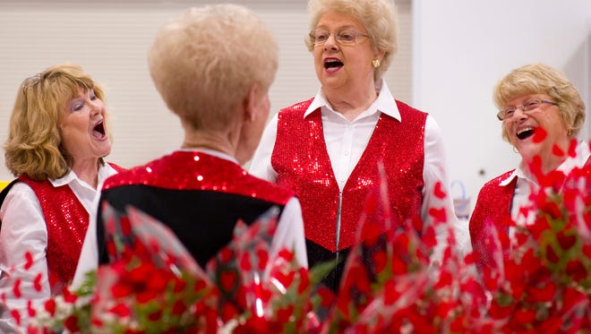DENNY SIMMONS / COURIER & PRESS Members of the Sweet Adelines (from left) Kathy Roberts, Karen Park and Linda Weber warm up before the 2016 singing Valentine deliveries.