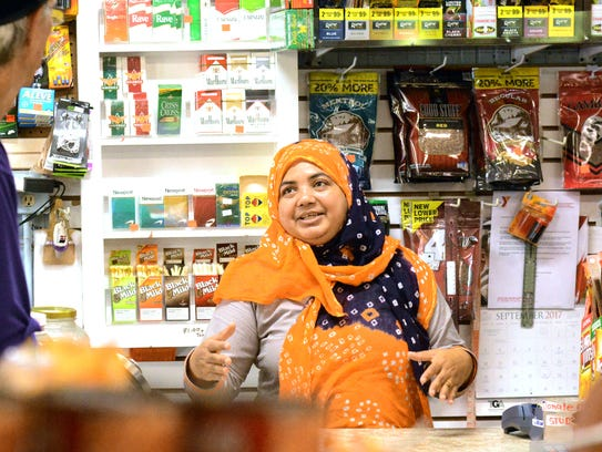 Kamrun Nahar of Halal Meat and Grocery, center, talks