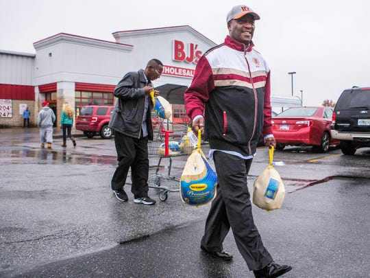 Norman Oliver (right) and his friend Tyrone Brown haul turkeys back to Brown's car at B.J.'s Wholesale Club in New Castle on Tuesday afternoon.