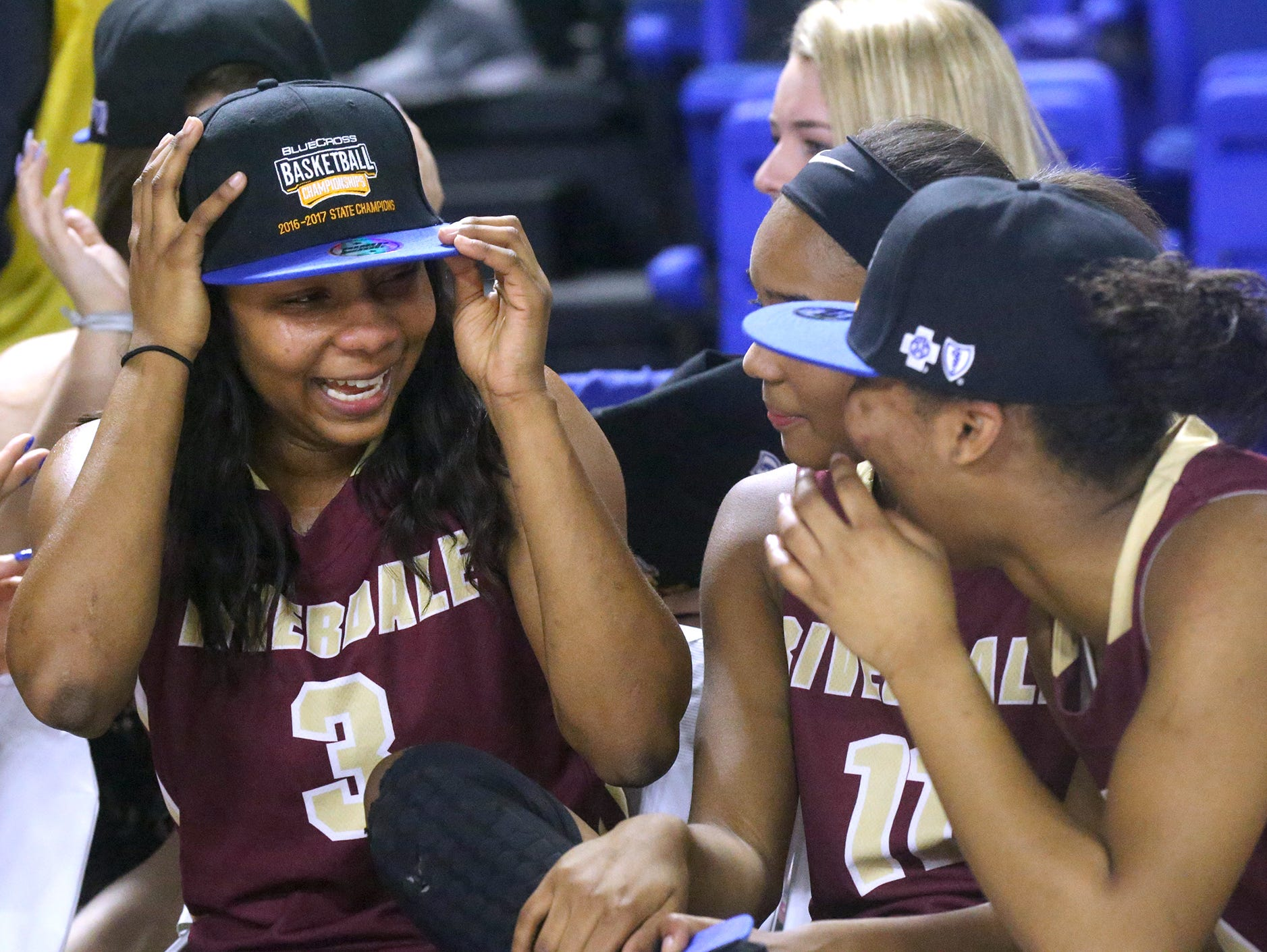 Riverdale's Anastasia Hayes (3) puts on her State Championship as she talks to her sisters and teammates Aislynn Hayes (11) center and Alasia Hayes (1) following the win over Memphis Central in the Championhip game of the Class AAA State Tournament on Saturday, March 11, 2017.